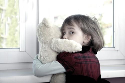 Напуганный ребенок с игрушкой у окна