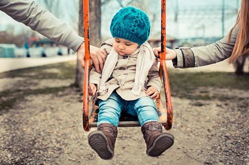 Ребенок на качелях и родители